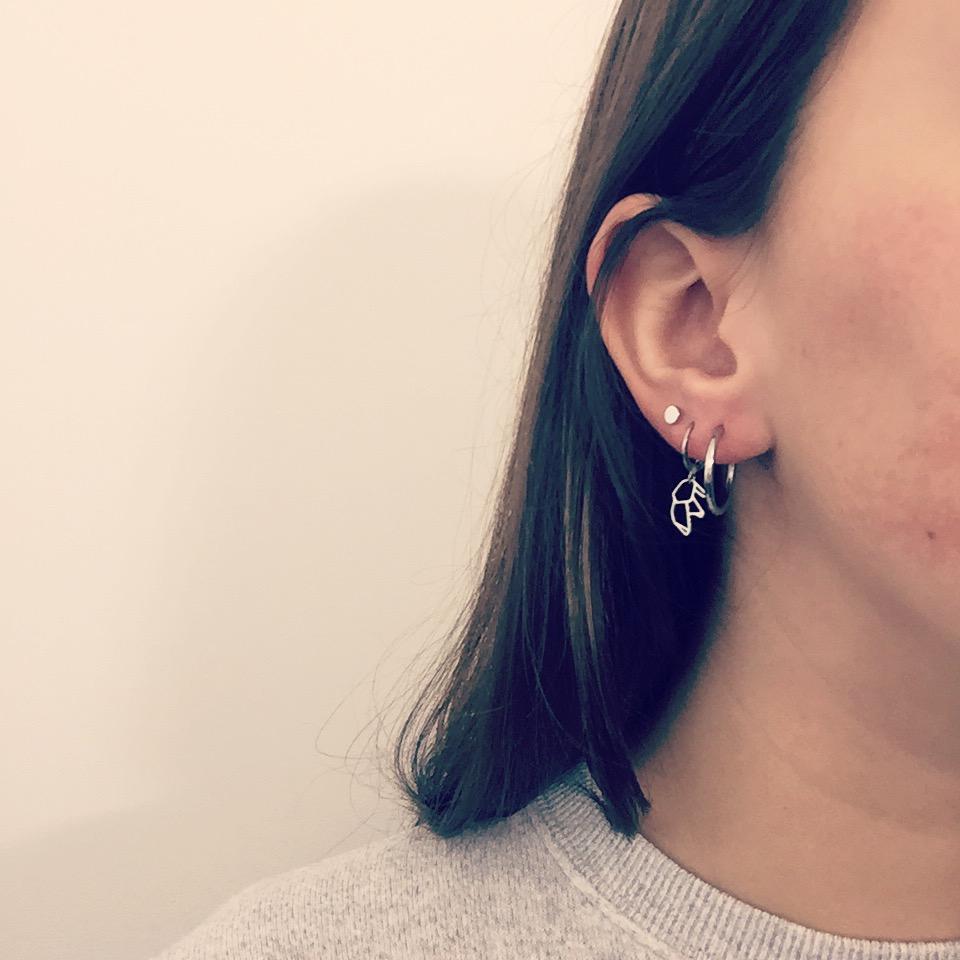 Meisje draagt drie soorten zilveren oorbelletjes