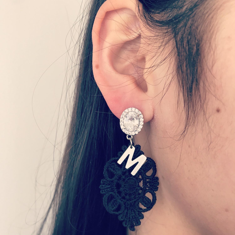 Meisje draagt zwarte kanten initial oorbellen met zilveren accenten