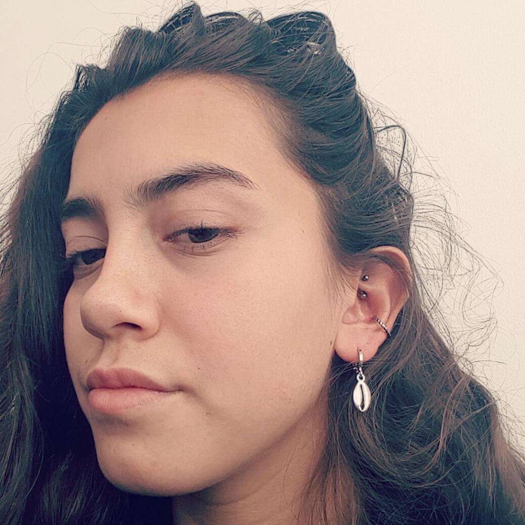 Meisje draagt zilveren schelp oorbellen