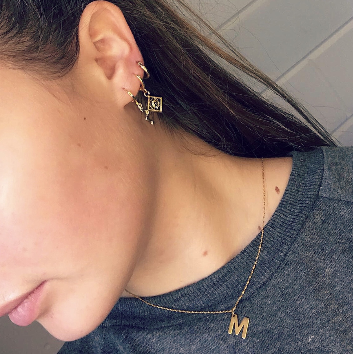 Meisje met blond haar draagt mix en match gouden sieraden van FINASTE