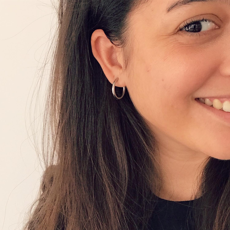 Meisje met bruin haar draagt zilveren basic oorringen