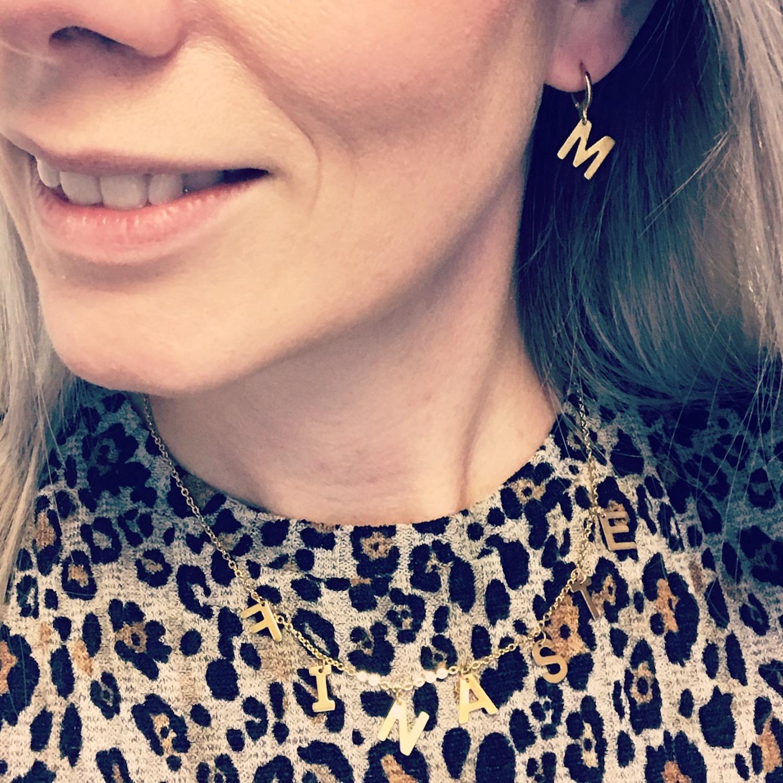 Blonde vrouw draagt gouden initial oorbellen