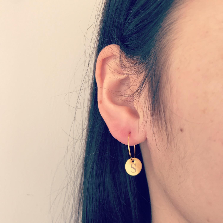 Meisje met donker haar met gouden graveerbare oorbelletjes