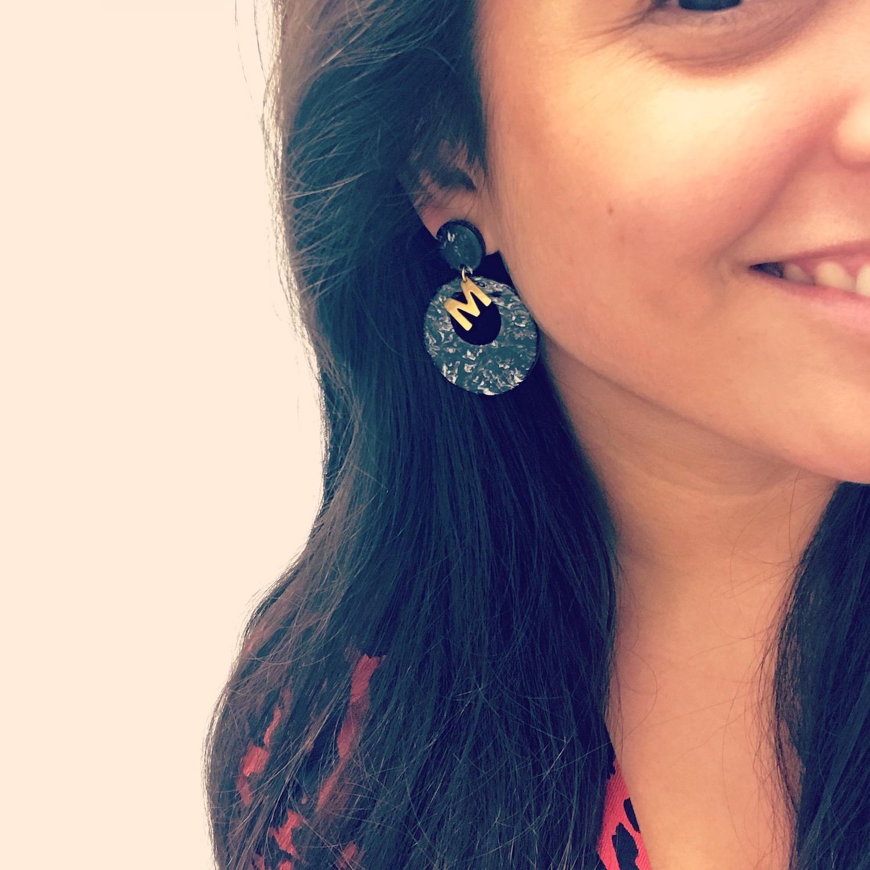 vrouw draagt initiaal oorbellen in zwart