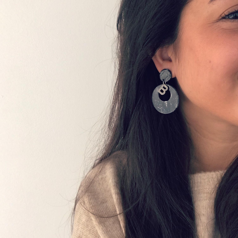 Meisje draagt zware statement oorbellen met zilveren initial