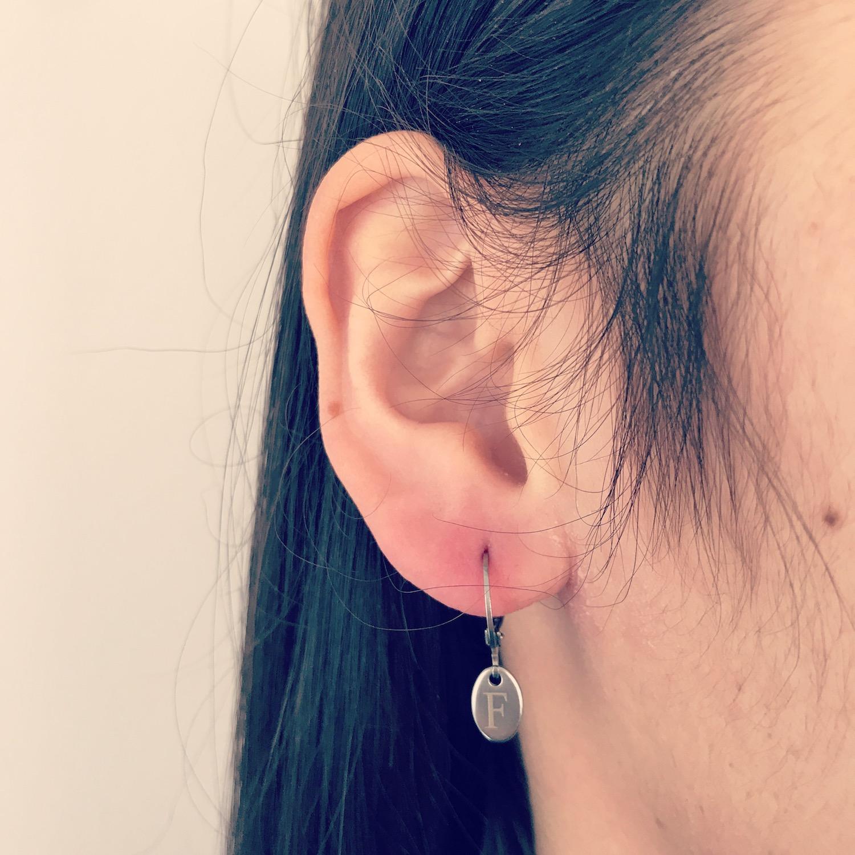 Meisje draagt zilveren graveerbare oorbellen