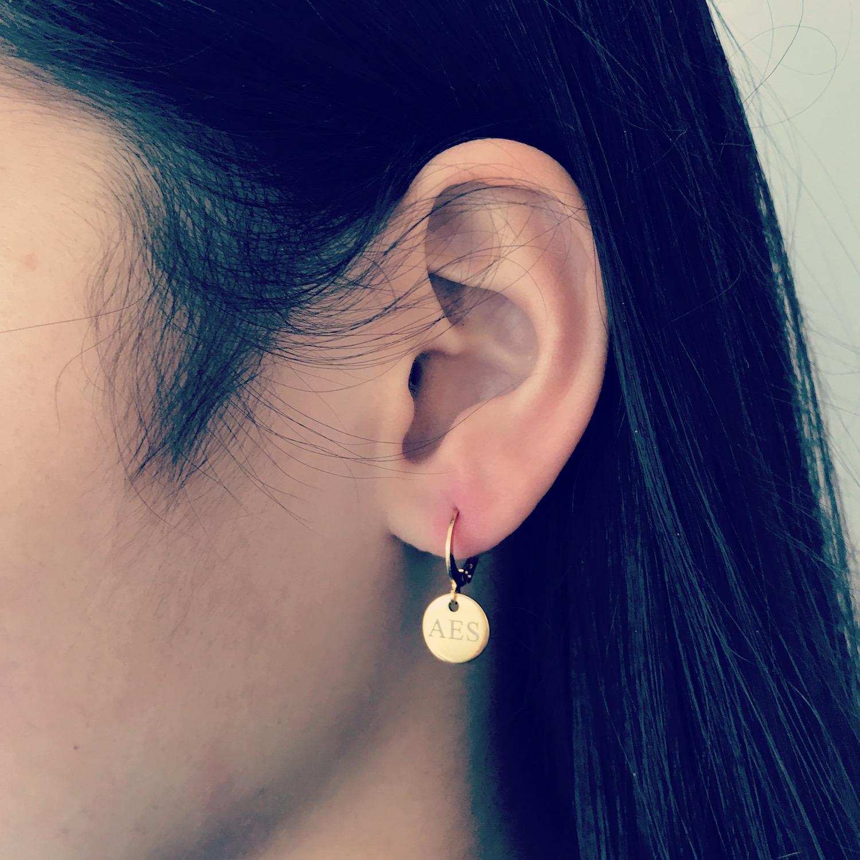 Meisje met donker haar en graveerbare gouden oorbellen met muntje