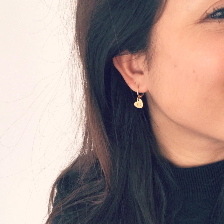 Meisje draagt gouden graveerbare hartjes oorbellen
