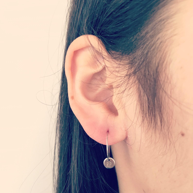 Meisje draagt zilveren oorbellen met graveerbaar muntje