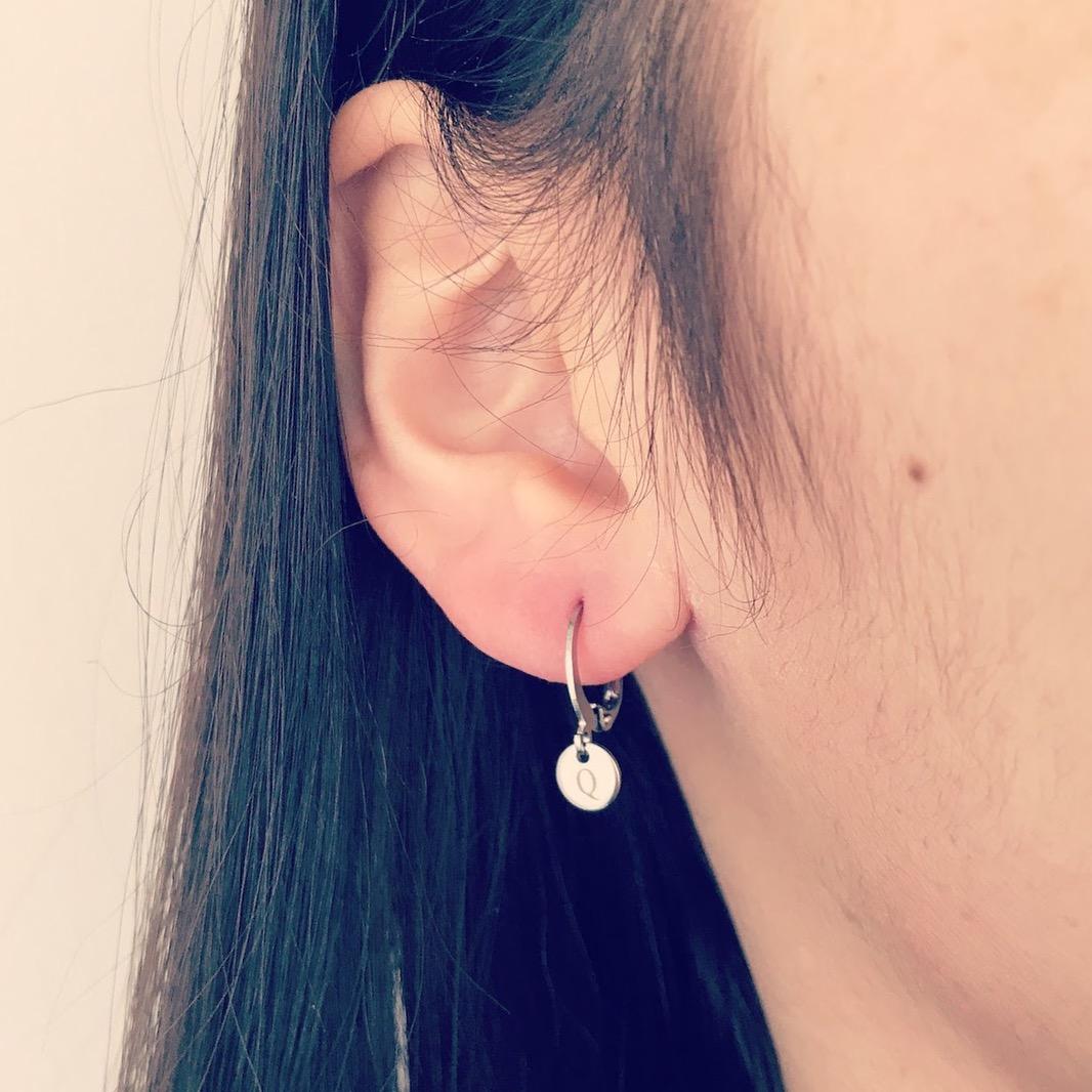 Meisje draagt zilveren oorbellen die je kunt graveren