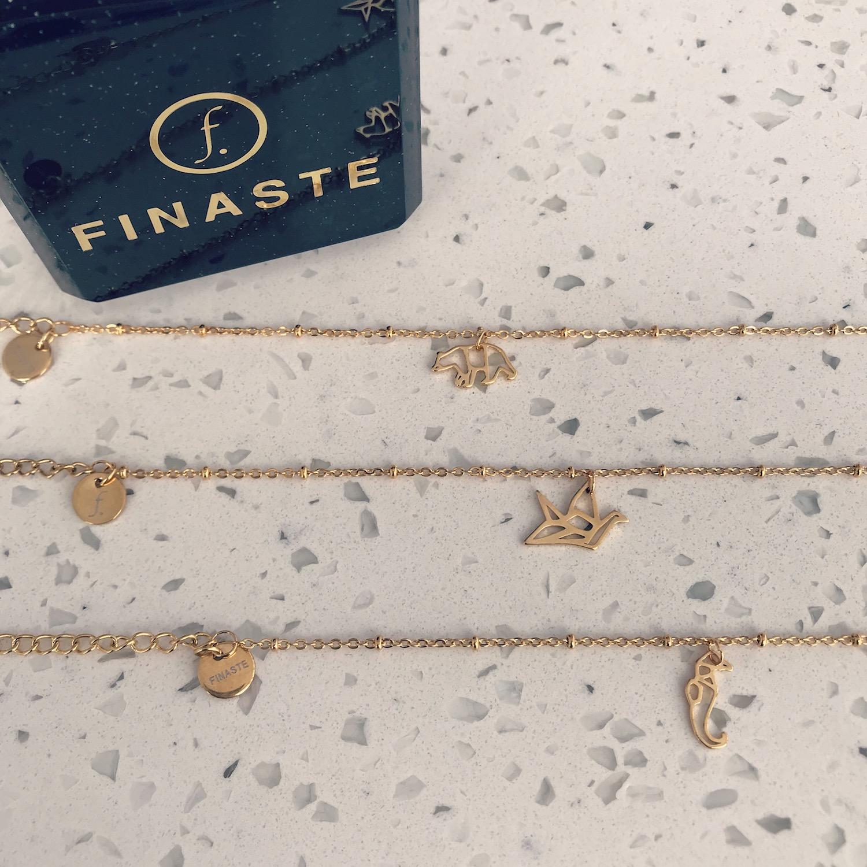 Gouden armbandjes met origami beestjes op een rij
