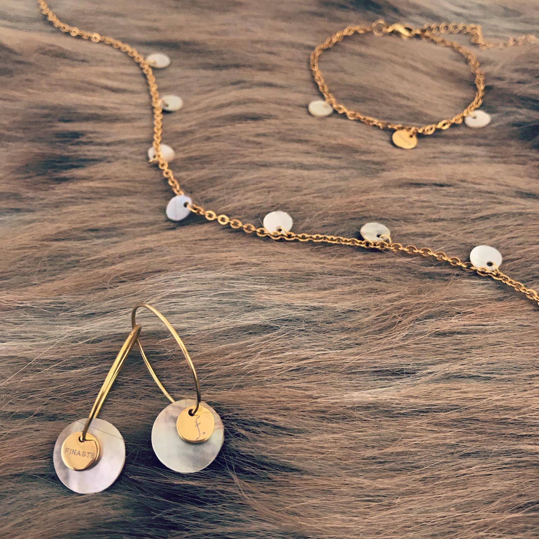 Minimalistische schelpjes sieraden op zachte achtergrond