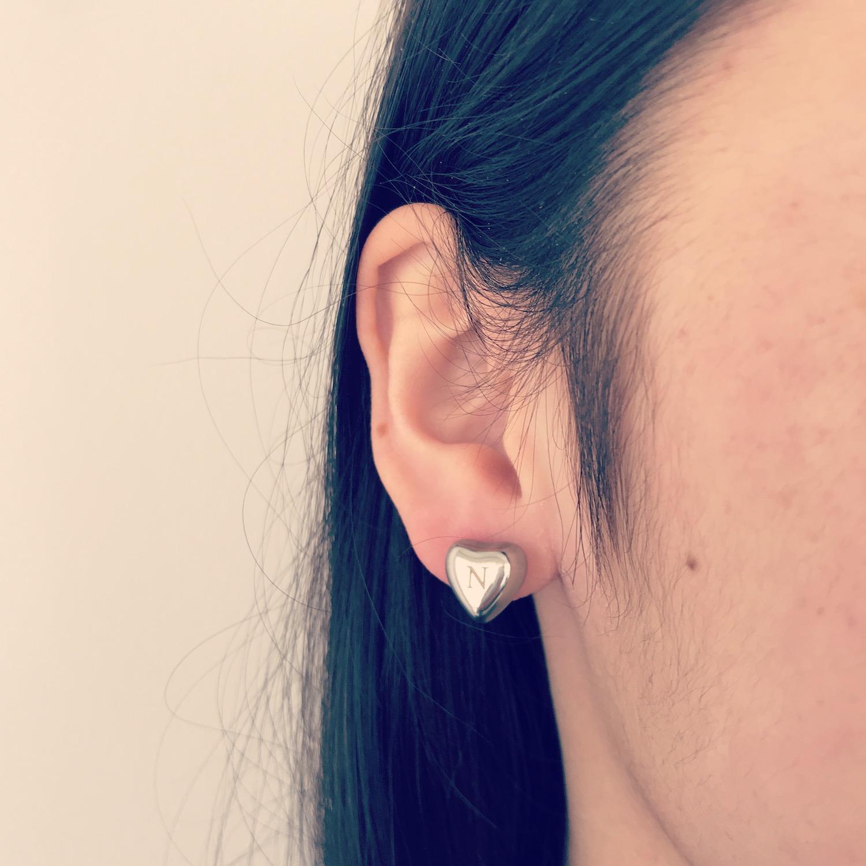 Meisje draagt zilveren graveerbare hartjes oorbellen
