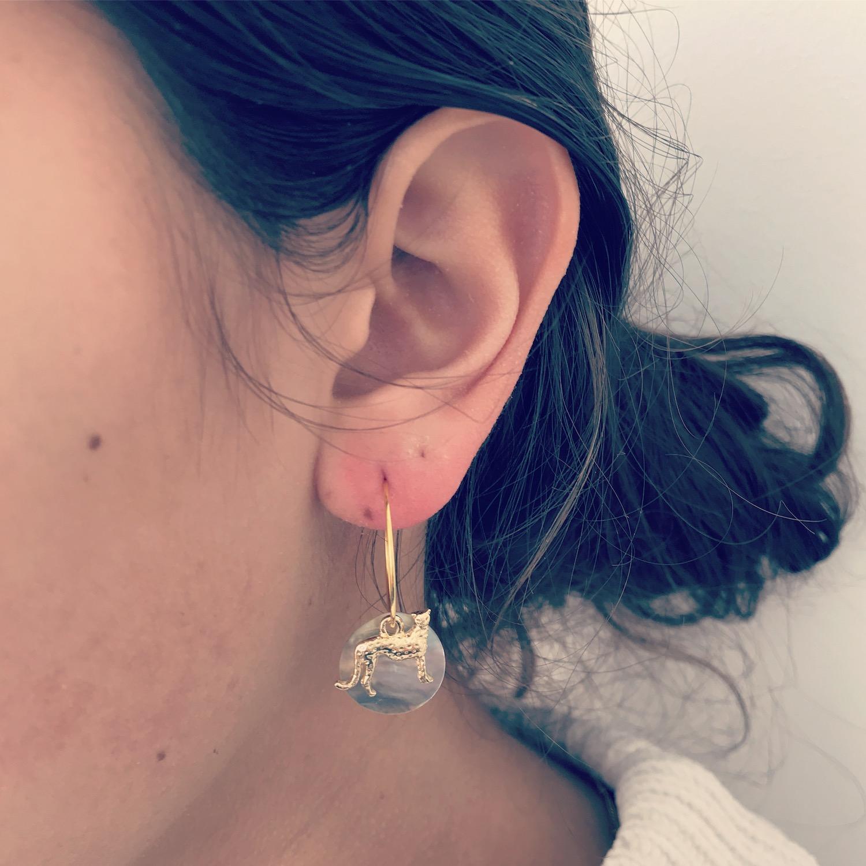 Gouden tijger oorbellen met schelpje bij meisje met donker haar