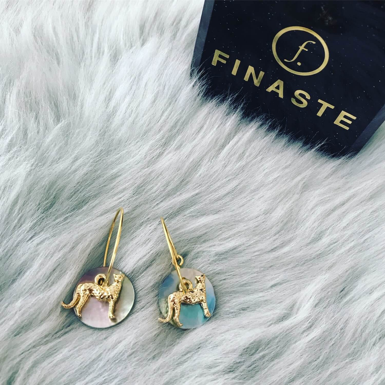 Gouden oorringen met schelpje en panter op zacht kleedje