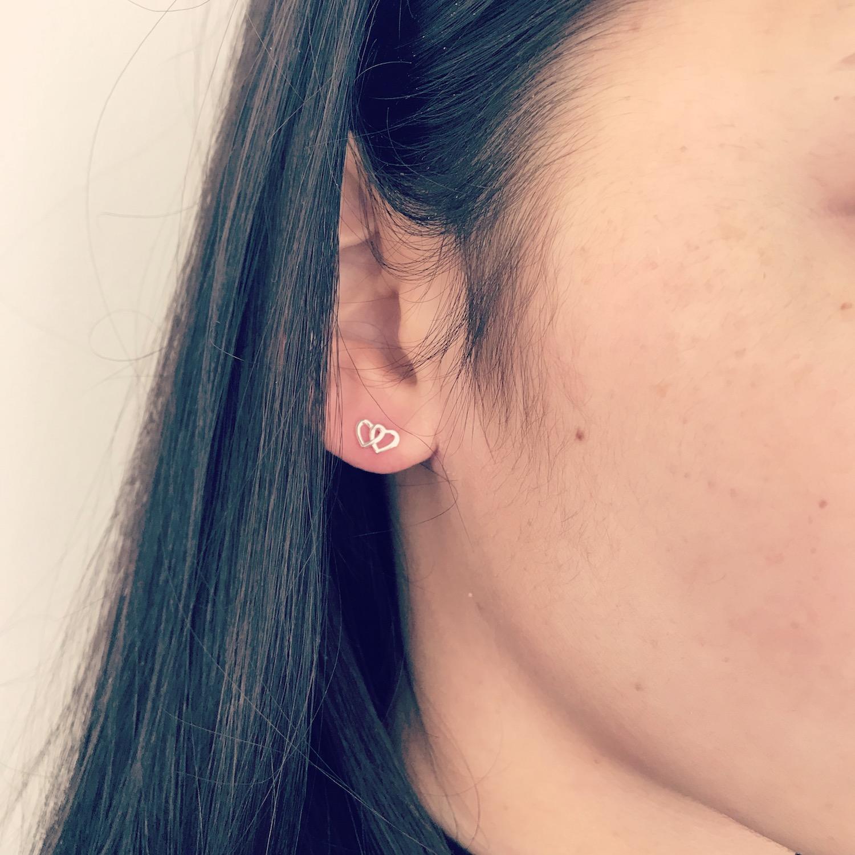 Zilveren dubbele hartjes stud oorbellen bij meisje met donker haar