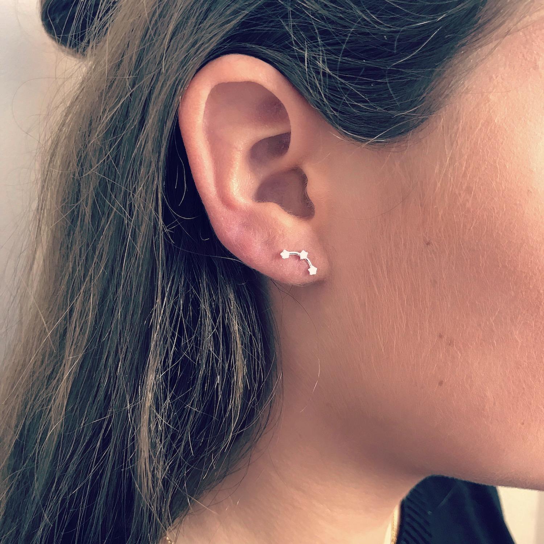 Zilveren sterretjes stud oorbellen bij meisje met bruin haar