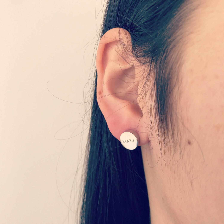 Meisje draagt zilveren graveerbare stud oorbellen