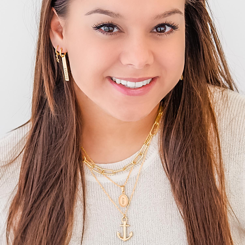 Gouden oorbellen met een lange hanger bij een vrouw met beige shirt