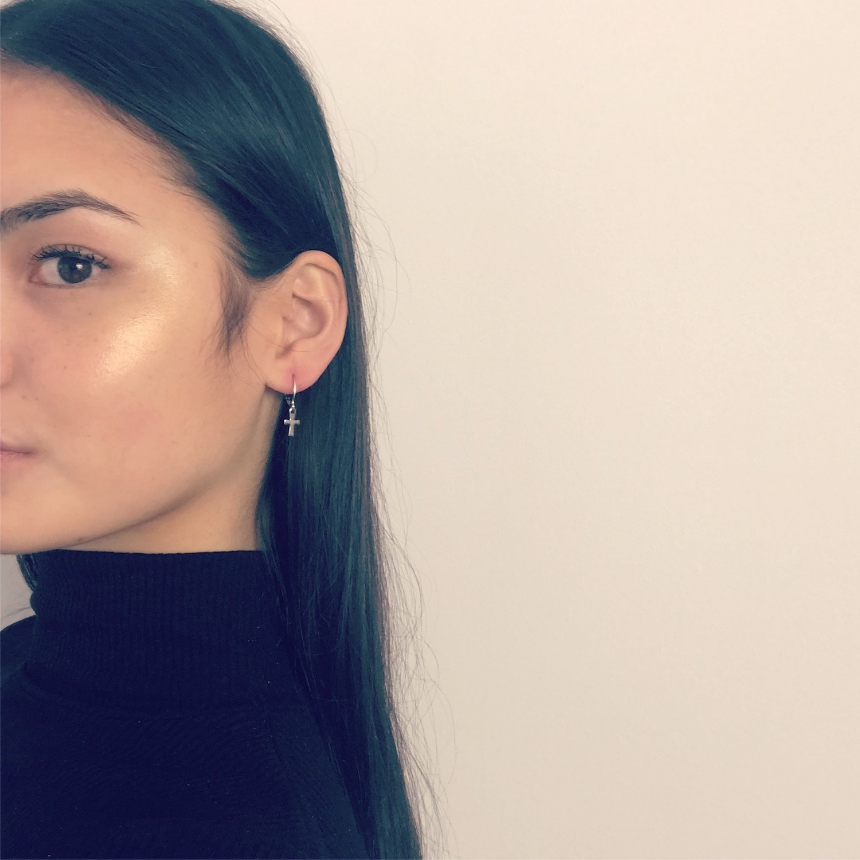 Meisje draagt zilveren oorbellen met kruisje