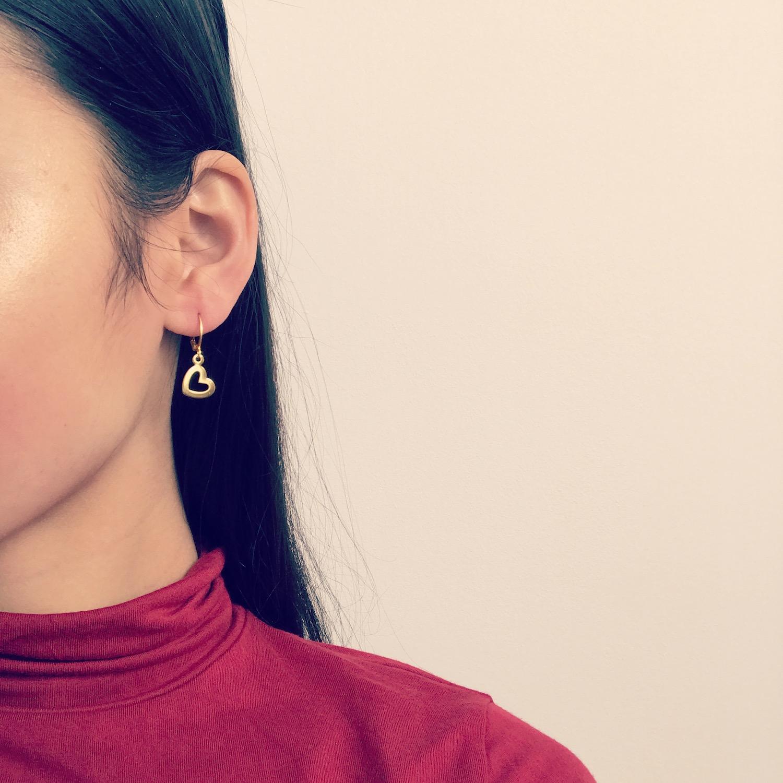Meisje draagt gouden oorbellen met hangertje in hartjes vorm