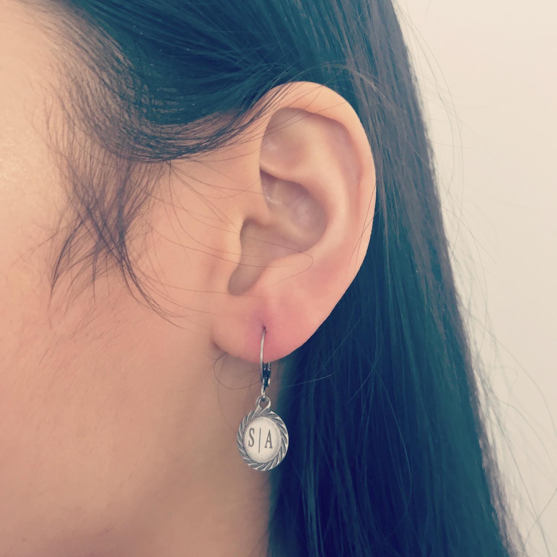 Meisje draagt vintage oorbellen met graveerbaar muntje