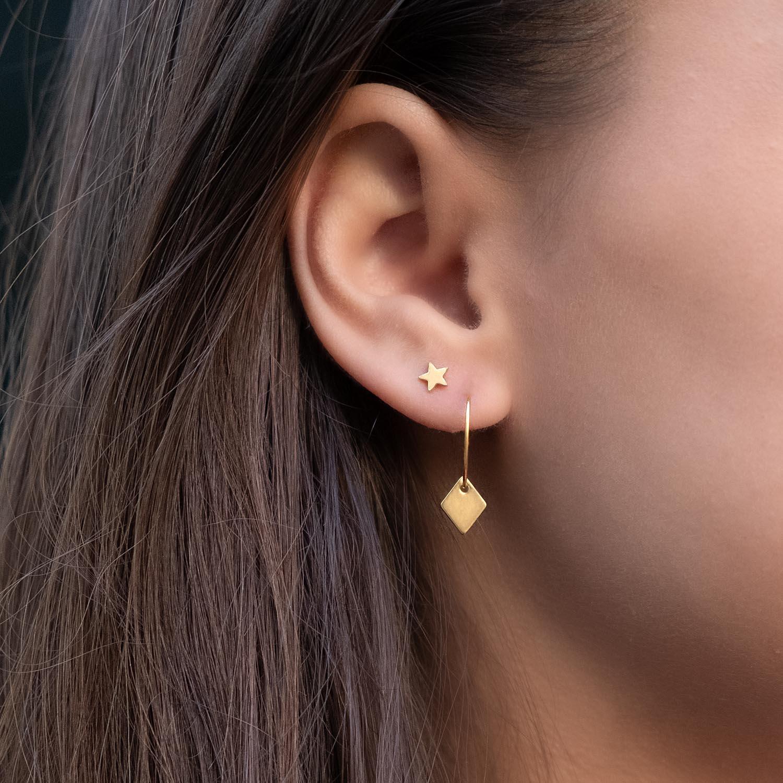 Vrouw draagt gouden stud oorbellen met ster en ruitje