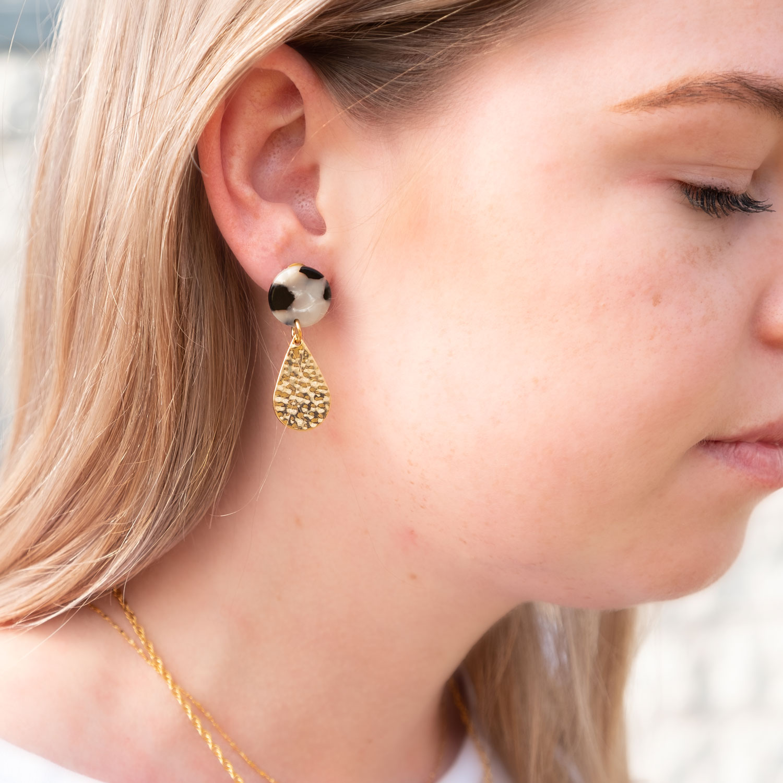 Meisje draagt gouden statement oorbellen met marble