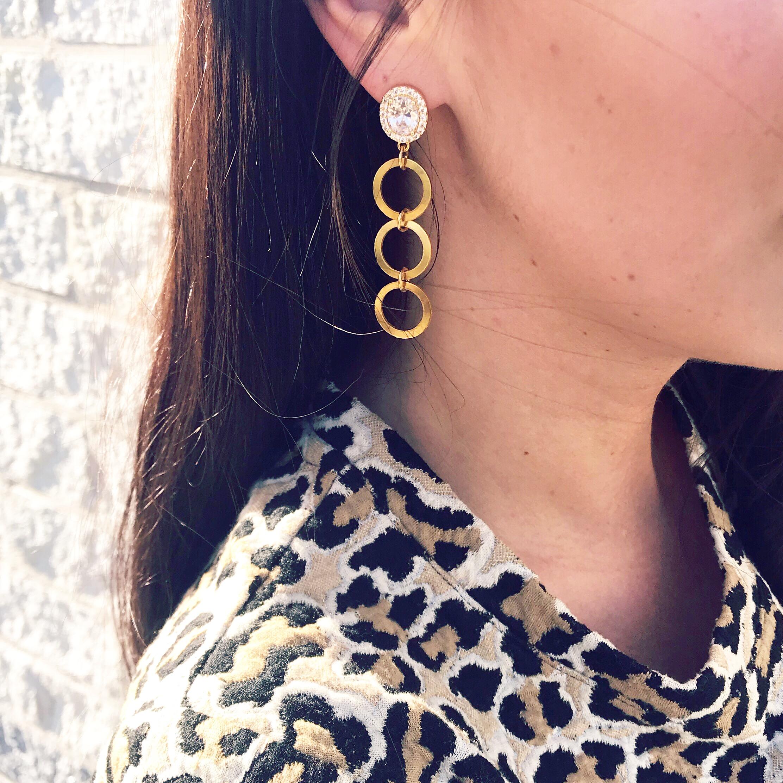 Meisje draagt gouden statement oorbellen met sparkle