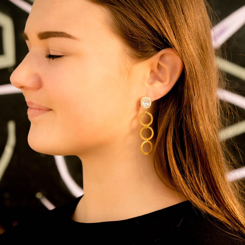 Meisje draagt gouden statement oorbellen met drie ringetjes
