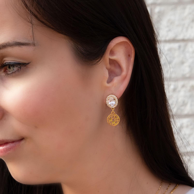 Vrouw draagt sparkle oorbellen goud met discobal