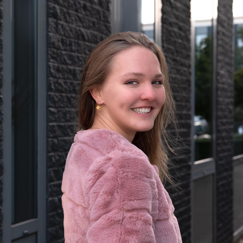 Vrouw draagt leuke gouden oorbellen met een roze jasje