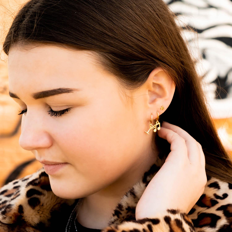 Vrouw draagt leuke party oorbellen in haar oor