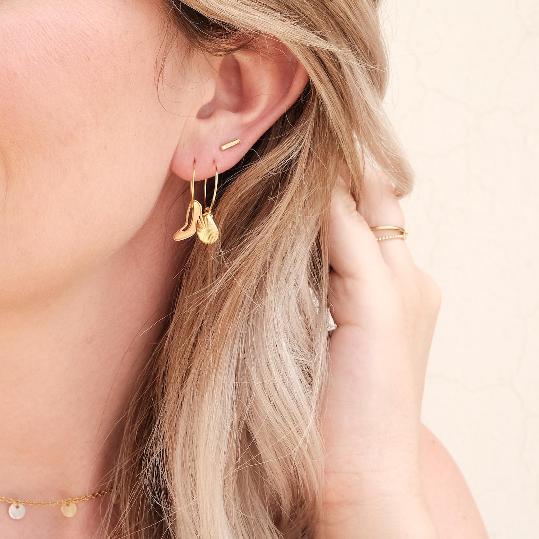 Gouden oorbellen bij vrouw met blonde haren