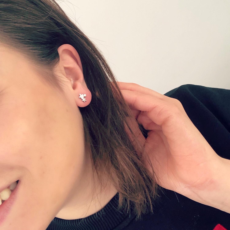 Meisje draagt zilveren sterretjes stud oorbelletjes