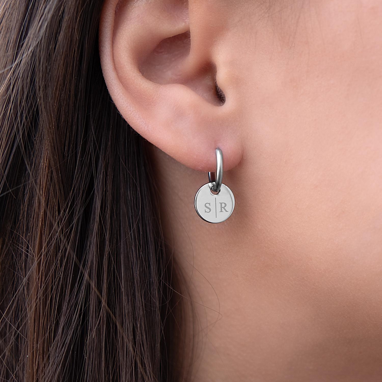 Zilveren initialen oorringetjes met letters in het oor met rondje
