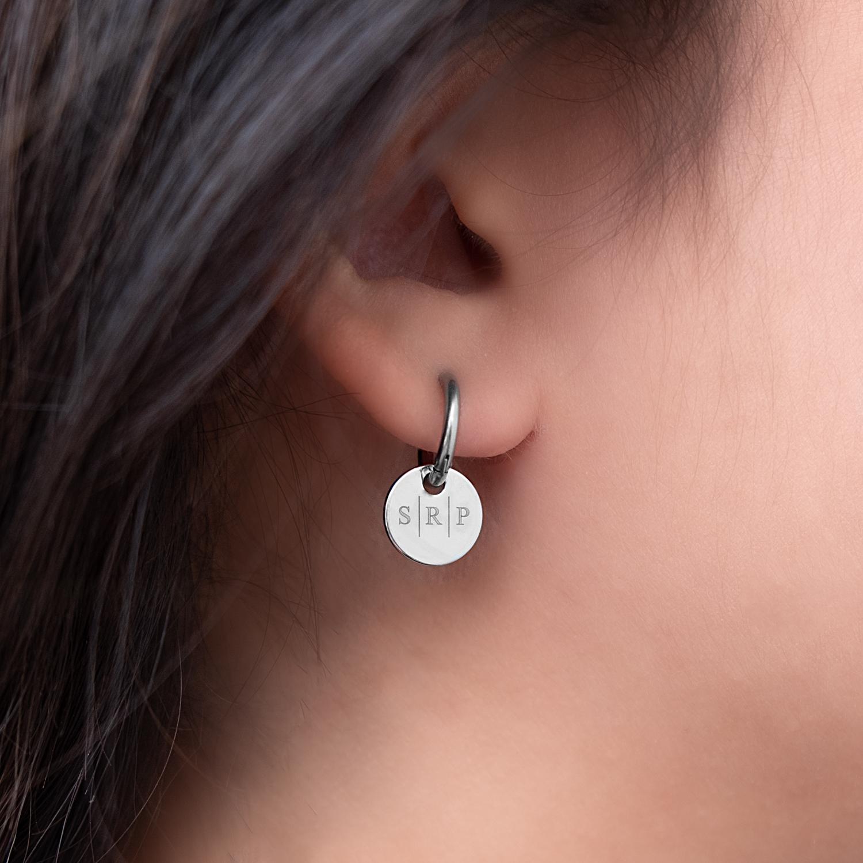 Oorbellen met letters in het oor met drie initialen