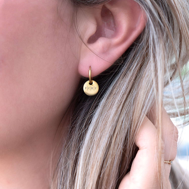 Gouden oorbelletjes met vier initialen in het oor