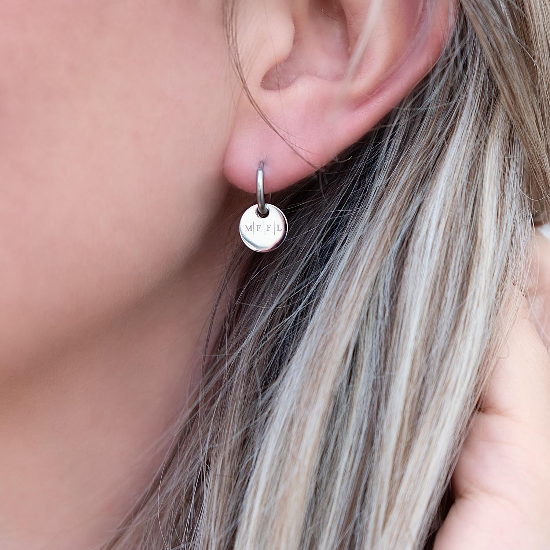 Vier initialen oorringetjes in het oor bij blond haar