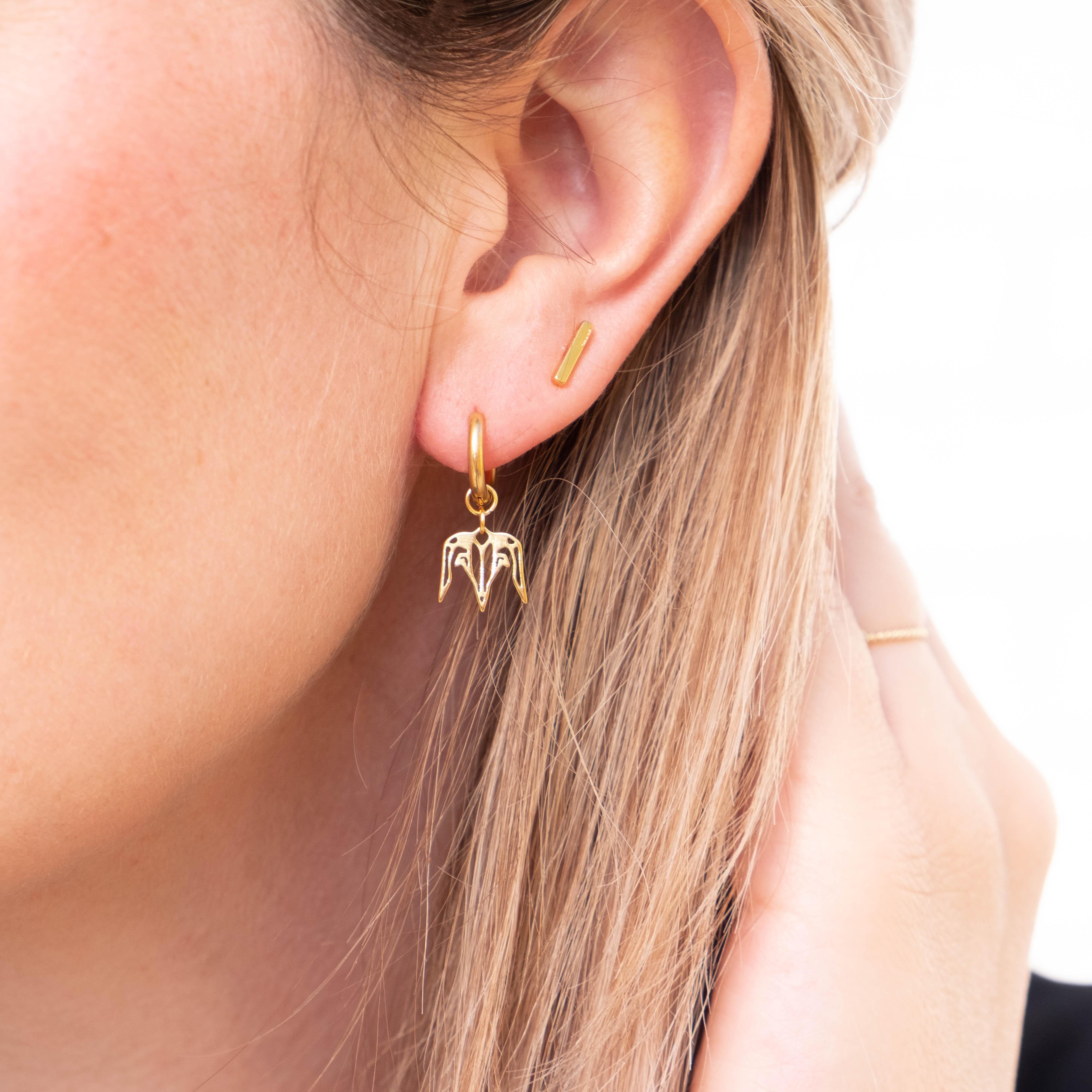 Gouden steenbok oorbel bij vrouw met blonde haren