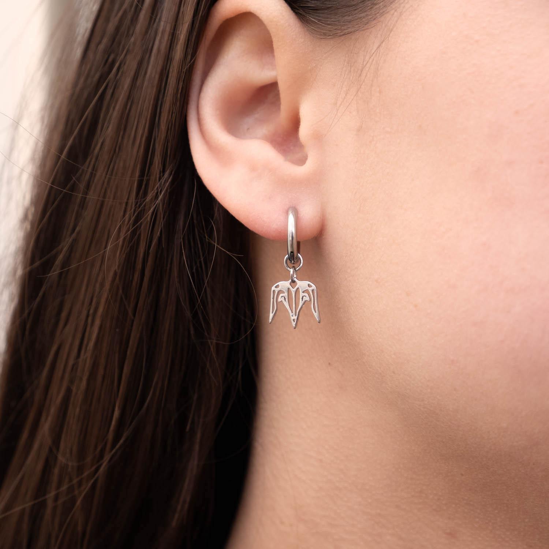 Zilveren steenbok oorbellen bij jonge vrouw