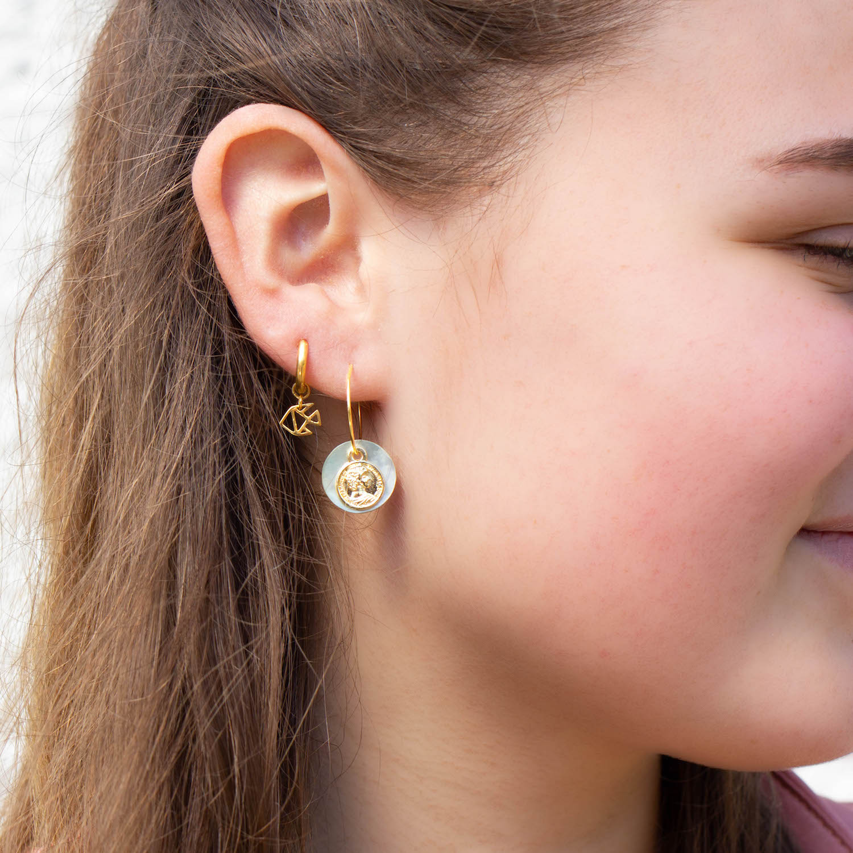 Vrouw met gouden oorbellen van sterrenbeeld Vissen