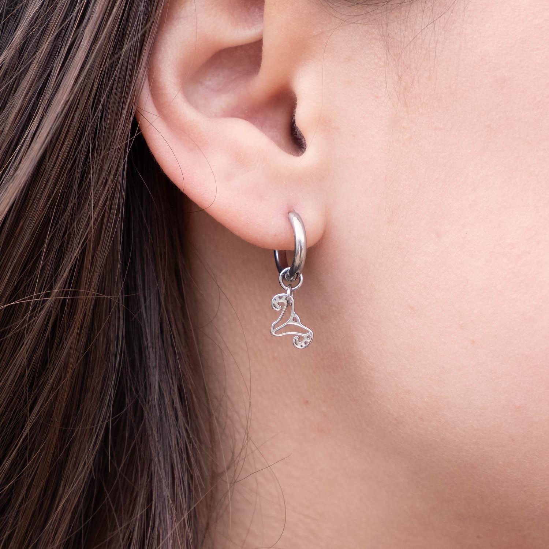 Zilveren ram oorbellen sterrenbeeld bij donker haar