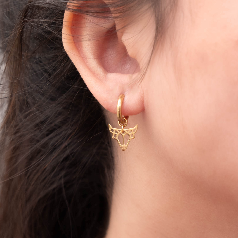 Vrouw draagt gouden stier oorbellen van sterrenbeeld
