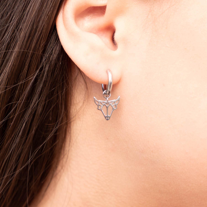 Vrouw draagt oorbellen van sterrenbeeld stier