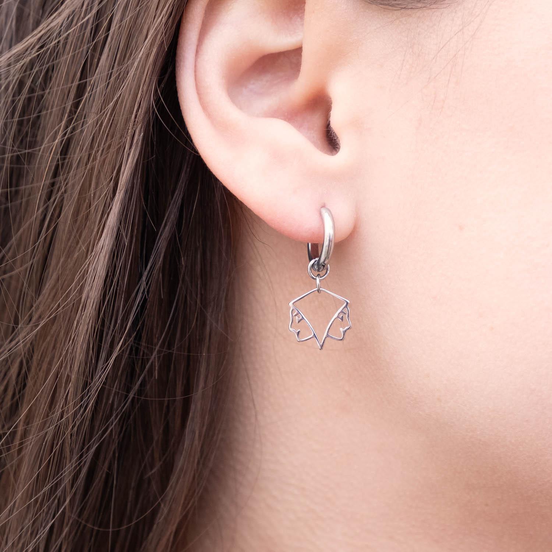 Vrouw draagt zilveren tweeling oorbellen in het oor