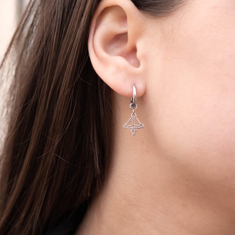 Vrouw draagt zilveren boogschutter oorbellen