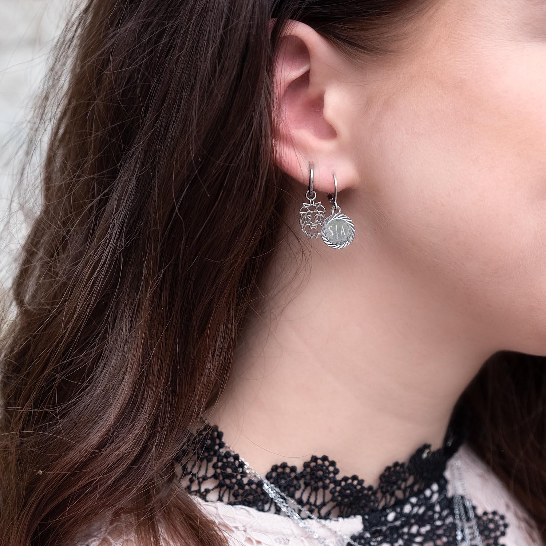 vrouw draagt zilveren leeuw oorbellen in het oor