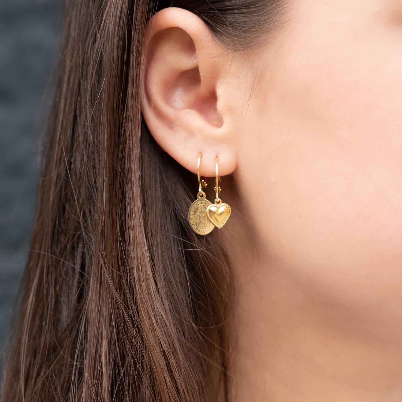 Vrouw draagt gouden earparty met hartje en maria oorbellen
