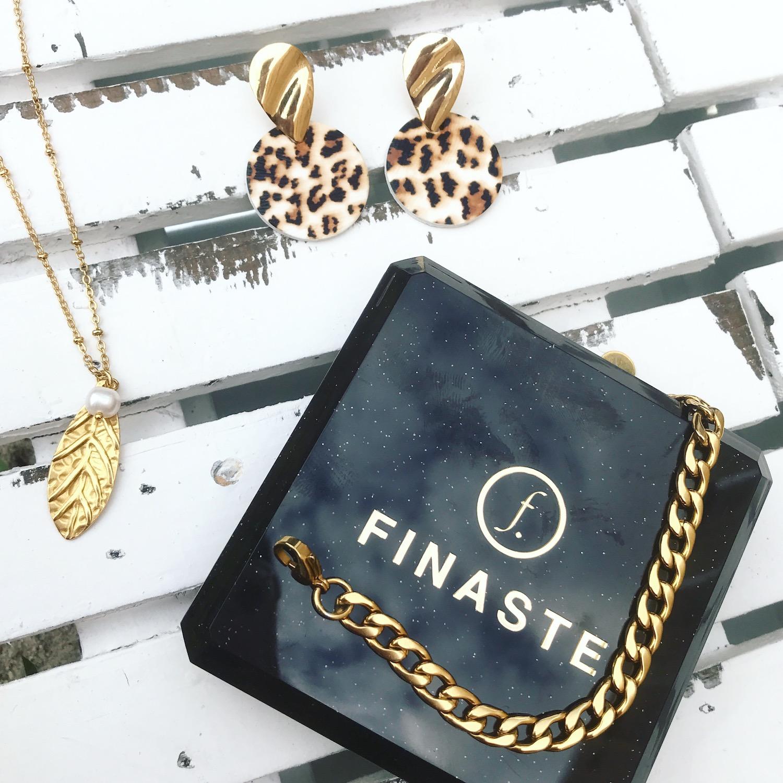Verschillende gouden sieraden op een plaatje met oorbellen